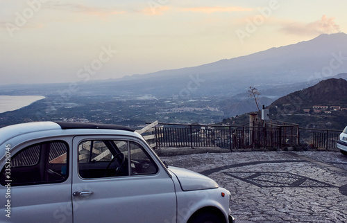 Vintage car parked by view of Mount Etna Wallpaper Mural