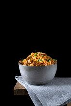 Pilaf With Meat In A Ceramic Bowl On The Edge Of The Table Against The Black Background. Traditional Oriental Cuisine Meal. Low Key Photo