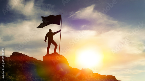 Obraz na płótnie Man with flag on top of the mountain against the sky