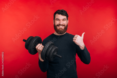 Photo of happy handsome young man holding dumbbell and showing thumbs up gesture Fototapet