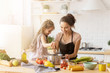 canvas print picture - Mother and daughter preparing tasty food at kitchen.