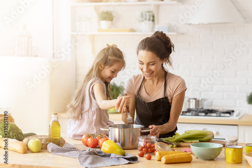 Foto Mother and daughter preparing tasty food at kitchen.