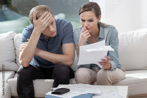 Fototapeta Stressed married couple looking frustrated, having no money to pay off their debts, managing family budget together obraz