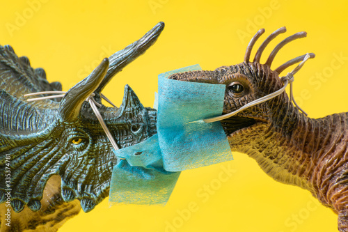 Photo Two plastic dinosaur toys with face masks kissing on  yellow background