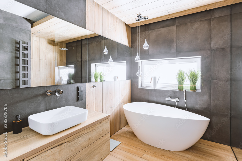 Fototapeta Stylish bathroom with wooden and concrete walls and white bath