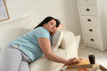 Lazy Overweight Woman With Pizza On Sofa At Home