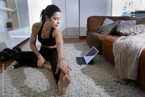 Giovane donna in tuta nera si allena in casa sul tappeto di casa con gli attrezz Wallpaper Mural