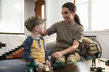 Soldier Mother Putting Camouflage Hat On Son In Living Room