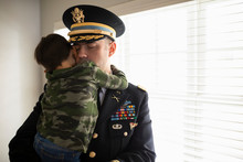 Affectionate Military Officer In Dress Uniform Holding Son