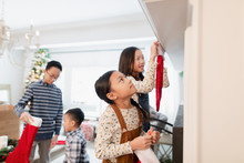 Sisters And Brothers Putting Up Christmas Stockings Over Fireplace