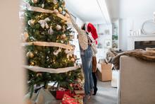 Sisters In Santa Caps Decorating Christmas Tree