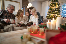 Grandparents Reading Bedtime Story To Granddaughters On Christmas