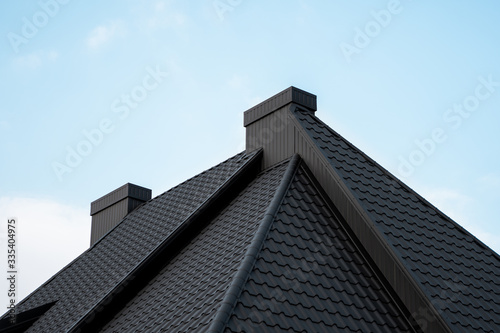 Fototapeta Black metal tile roof. Roof metal sheets. Modern types of roofing materials. Roof of the house, metal roof tile against the blue sky. Building. obraz