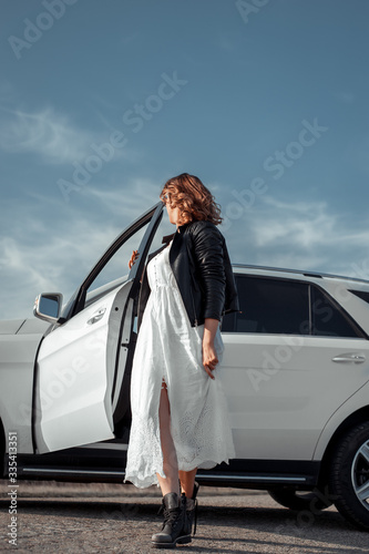 Woman on the background of a car Fototapeta