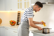 Handsome Man Cooking Pasta On Stove In Kitchen