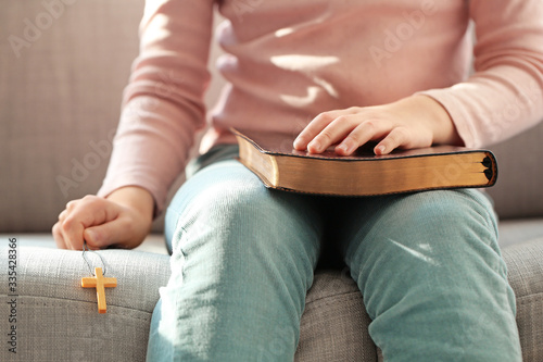 Cute little Asian girl with Bible at home Canvas Print