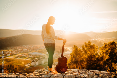 Young guitarist holding an acoustic guitar and looking to sunset Canvas Print