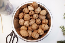 Walnuts In A Chromed Bucket On A White Background. View From Above