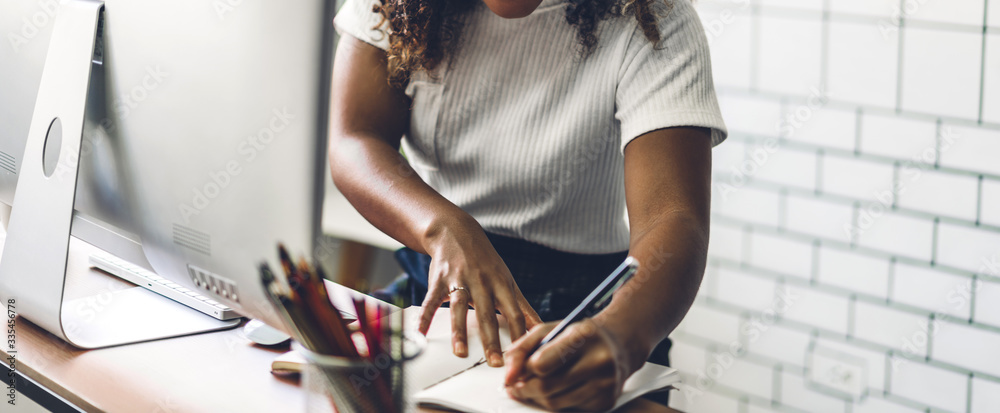 Fototapeta Portrait of african american black woman relaxing using technology of desktop computer while sitting on table.Young creative african girl working and write on book at home.work from home concept
