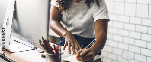 Fototapeta Portrait of african american black woman relaxing using technology of desktop computer while sitting on table.Young creative african girl working and write on book at home.work from home concept obraz
