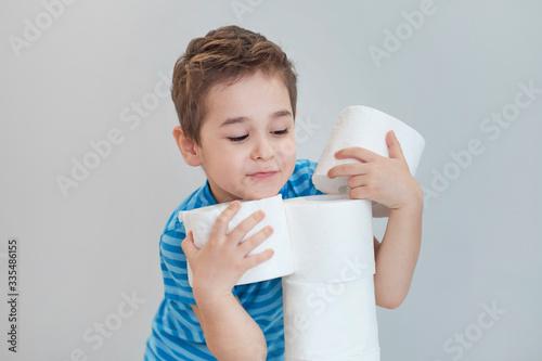 Fotografia boy builds a tower of toilet paper