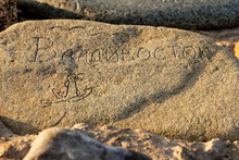 Vladivostok, Russia - March, 21, 2020: A Stone With The Word Vladivostok Embossed On It, An Anchor And Flying Gulls Lying On The Tokarevskaya Spit Leading To The  Tokarevsky Lighthouse In Vladivostok.