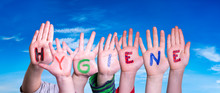 Kids Hands Holding Colorful English Word Hygiene. Blue Sky As Background
