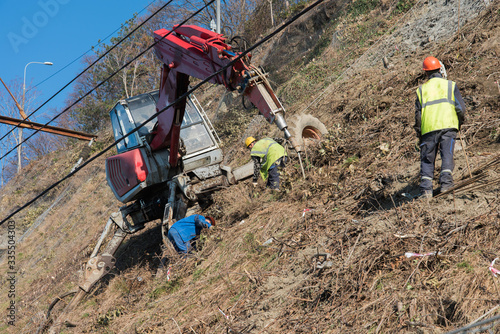 Fototapeta Workers strengthen the mountainside with a metal mesh that prevents rockfall on the road