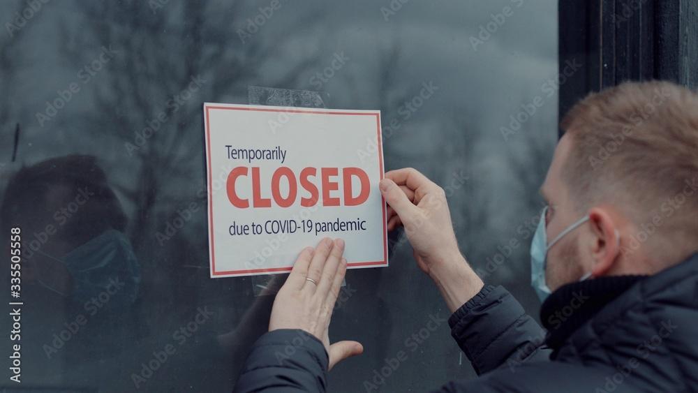 Fototapeta Caucasian male wearing medical mask puts a Temporary closed due COVID-19 pandemic sign on a window. Coronavirus pandemic, small business shutdown