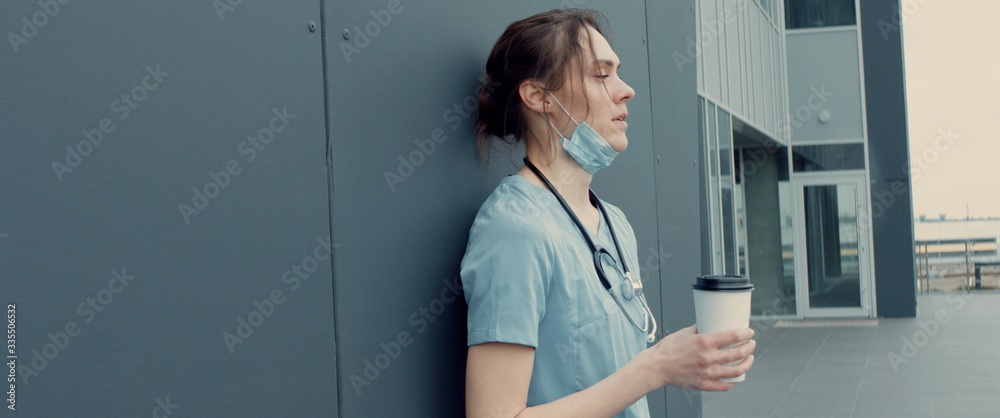 Fototapeta Portrait of tired exhausted nurse or doctor having a coffee break outside in the morning. COVID-19, Coronavirus pandemic. ARRI Alexa Mini