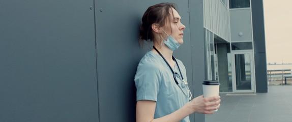 Portrait of tired exhausted nurse or doctor having a coffee break outside in the morning. COVID-19, Coronavirus pandemic. ARRI Alexa Mini