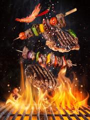 Ukusni goveđi odresci i ražnjići koji lete iznad goruće rešetke od lijevanog željeza vatrenim plamenom. Koncept zamrzavanja roštilja.