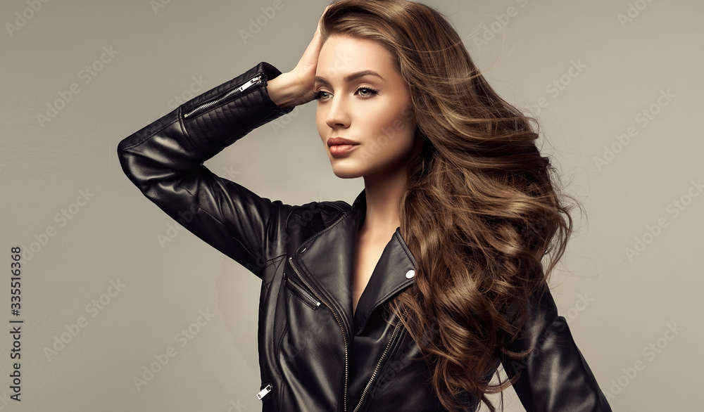 Fototapeta Beautiful stylish woman wearing  black leather jacket. Fashionable and self-confident girl with long curly hair. Clothing, style and fashion