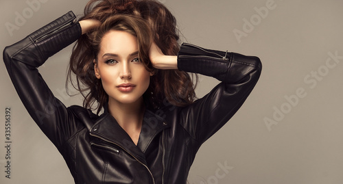 Beautiful stylish woman wearing black leather jacket. Fashionable and self-confident girl with long curly hair. Clothing, style and fashion