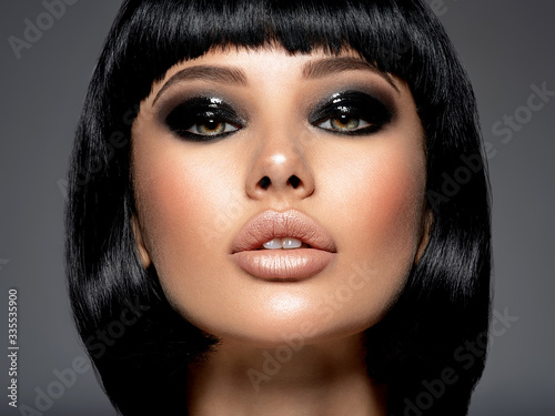 Beautiful fashion woman with a bob hairstyle looks to the camera Fotobehang