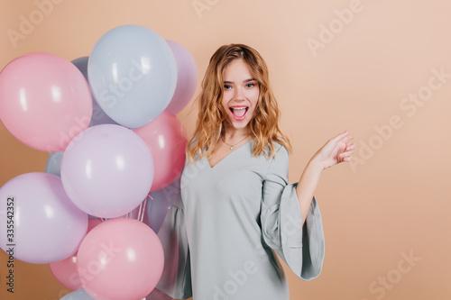 Fototapeta Charming fair-haired birthday girl posing with pleasure on light background