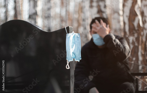 Photo A man in a medical mask mourns, holding on to his head, sitting at the tombstone
