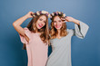 canvas print picture - Winsome young woman in pink attire having fun with best friend in flower wreath. Studio shot of two ladies isolated on blue background with charming smile.