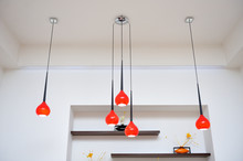High Hanging Chandelier With Red Shades On A White Wall Background