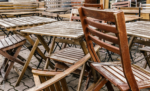 Photo Wooden chairs and tables stored, locked and chained early morning