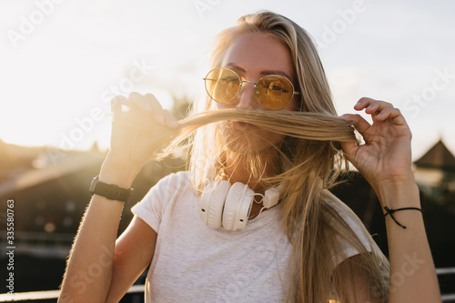 Photographie Inspired european woman playing with her blonde hair in sunny day