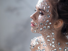 Fantastic Fashion Portrait Of A Young Beautiful Woman With Transparent Crystals On Her Face And Shoulders.