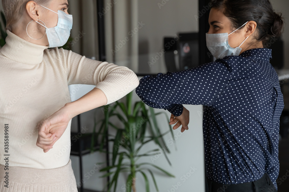 Fototapeta Smiling young healthy mixed race female colleagues wearing facial medical masks greeting each other by bumping elbows gesture at workplace keeping social distance, preventing spreading covid19 virus.