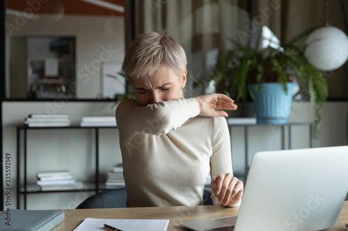 Foto Front view young female manager with short haircut coughing or sneezing in elbow while working on laptop in office room