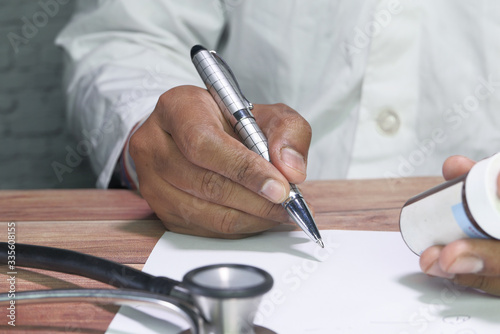 Mid section of doctor writes prescription to patient at worktable Canvas-taulu