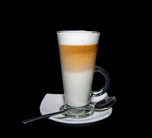 A Finished Triple Layered Latte Coffee Served With Plate And Spoon
