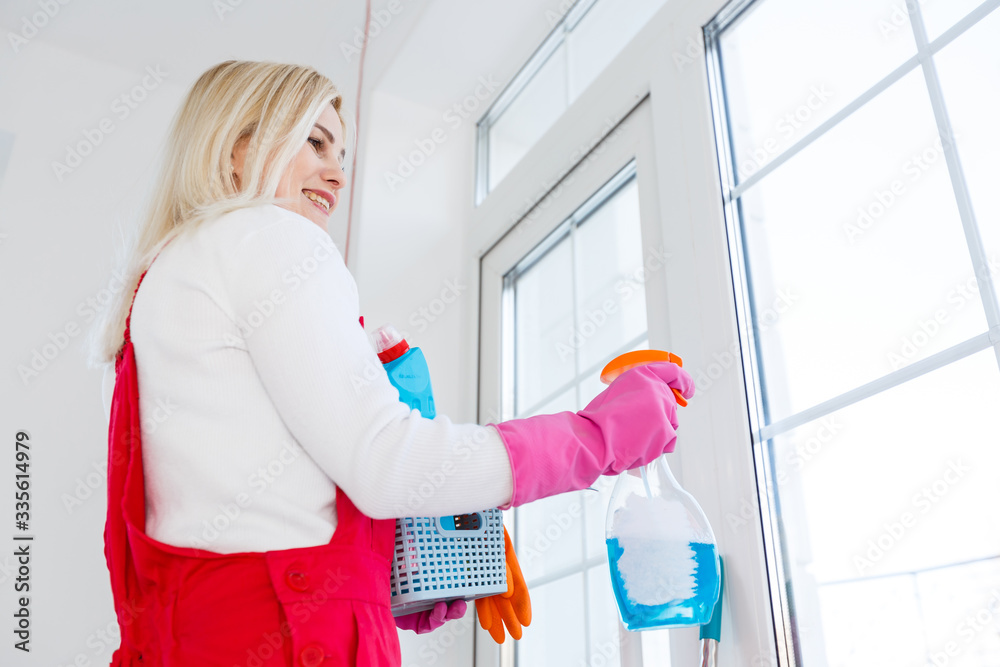 Fototapeta Cleaning lady with a bucket and cleaning products on office background. - obraz na płótnie