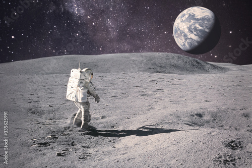 Canvas Print Astronaut on rock surface with space background