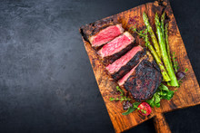 Barbecue Dry Aged Wagyu Entrecote Beef Steak With Lettuce And Green Asparagus As Top View On An Old Rustic Wooden Cutting Board With Copy Space Left