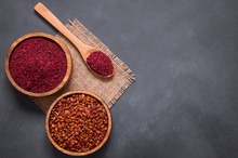 Dried Ground Red Sumac Powder Spices In Wooden Spoon With Sumac Berries On Rustic Table. Healthy Food Concept